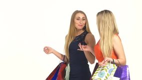 Two attractive girls friends going shopping with. Two sexy, beautiful, attractive girls friends going shopping with shopping bags  and talking about something on stock video footage
