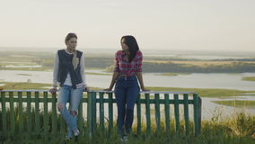 Two attractive girls friends young female standing on high hill at summer evening stock footage