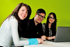Two attractive girls and a guy working in office. With green background Stock Images