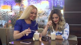Two attractive girls have fun chatting in a cafe stock video footage