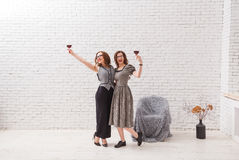 Two attractive girls, having fun and drinking red wine on party. Fashionable dressed with beautiful wavy hair. On loft. White brick wall Royalty Free Stock Images