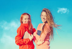 Two attractive girls having fun outdoors enjoying fresh air on windy summer day Royalty Free Stock Images