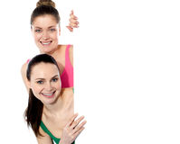 Two attractive girls holding blank whiteboard. Smiling at camera Royalty Free Stock Images
