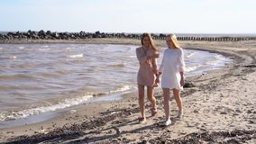 Two girls holding hands walking along the coastline, smiling and laughing. Two attractive girls holding hands walking along the coastline, smiling and laughing stock video