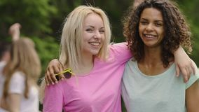 Two attractive girls hugging, looking into camera, young people having fun. Stock footage stock footage