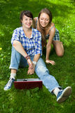 Two attractive girls with a laptop in the park stock photo