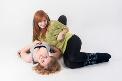 Two attractive girls lie and have fun Stock Photos