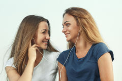 Two attractive girls listening to music. Against the sky Royalty Free Stock Image