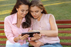 Two attractive girls listening to music. Two attractive girls listening music on the bench Stock Image