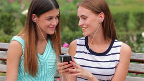 Two attractive girls listening to music. On the smartphone. Young woman enjoying the music sitting on the bench in the city. Rest and relax after shopping stock video