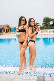Two attractive girls with long hair are posing near pool on the sun and drink cocktails. They wear swimsuit with sunglasses. They. Two attractive girls with long Royalty Free Stock Images
