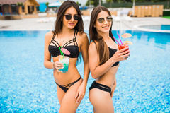 Two attractive girls with long hair are posing near pool on the sun and drink cocktails. They wear swimsuit with sunglasses. They Royalty Free Stock Photos