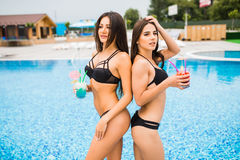 Two attractive girls with long hair are posing near pool on the sun and drink cocktails. They wear swimsuit with sunglasses. They Stock Photo