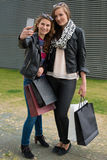 Two attractive girls making a selfie after. Two attractive young women making a selfie outside of the shopping mall carrying their bags Royalty Free Stock Photography