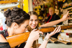 Two attractive girls playing shooting games at. German funfair Oktoberfest. Both wearing traditional Dirndl dresses, the one in front having an Asian touch royalty free stock images