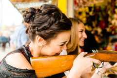 Two attractive girls playing shooting games at Royalty Free Stock Photo