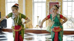 Two attractive girls in a sari dance a national dance