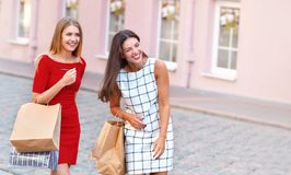 Two attractive girls with shopping bags are walking by city. Two attractive girls with shopping bags are walking by old city street. Lifestyle, friendship and Stock Photo