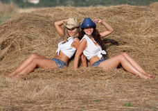 Two attractive girls sitting on haystack Royalty Free Stock Photography