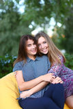 Two attractive girls sitting next to each other in chair, smilin Royalty Free Stock Photos