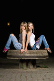Two attractive girls sitting on a stone. Bench Royalty Free Stock Photos