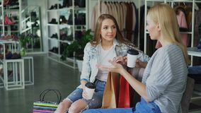Two attractive girls sitting and talking in women`s clothing store after shopping. Stylish colourful garments, shoes and. Two attractive girls sitting together stock video