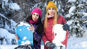 Two attractive girls snowboarders are among snowy fir trees in the winter and keep snowboards hands. Close-up portrait Stock Photos