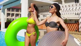 Two attractive girls in sunglasses walking wih inflatable tubes by the pool and smiling. Pretty women having a pool. Party. Slowmotion shot stock video