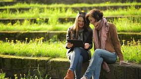Two Attractive Girls are Using Tablet Outdoors Sitting in the Park. Female Friends are Looking at the Screen of stock footage