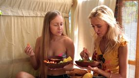 Two attractive girls on vacation eating vegan food stock footage