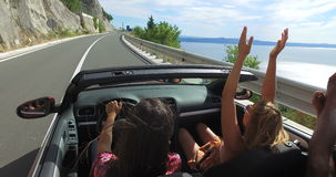 Two attractive girls waving their arms driving in convertible car with friends. Two attractive girls waving their arms and having fun while driving in stock video