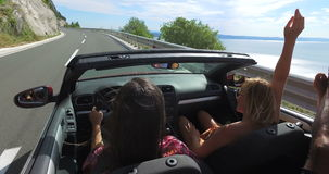 Two attractive girls waving their arms driving in convertible car with friends stock video footage