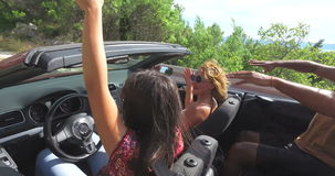 Two attractive girls waving their arms driving in convertible car with friends. Two attractive girls waving their arms while driving in convertible car with stock footage