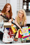 Two attractive happy girls out shopping. Two attractive happy teenager girls with colorful shopping bags Royalty Free Stock Photography