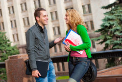 Two attractive happy students. Talking at campus Royalty Free Stock Photo