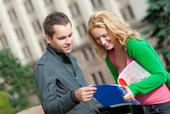 Two attractive happy students talking. At campus Stock Photos