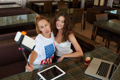 Two attractive ladies best friends posing while making photo with cell telephone camera during rest in restaurant, Stock Image