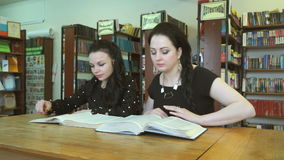 Two attractive ladies reading books at library stock video
