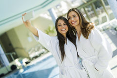 Two attractive ladies taking a selfie next to a swimming pool Royalty Free Stock Photos