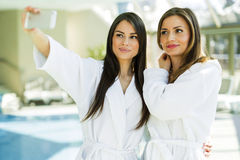Two attractive ladies taking a selfie next to a swimming pool Royalty Free Stock Images