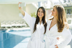 Two attractive ladies taking a selfie next to a swimming pool Stock Images