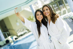 Two attractive ladies taking a selfie next to a swimming pool Royalty Free Stock Photography