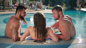 Two attractive man with young beautiful woman relaxing in the swimming pool stock video