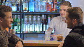 Two attractive men relaxing and talking in a bar. The camera moves from left to right. Two attractive men sits on a chairs near the bar. Two friends are talking stock video