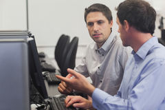 Two attractive men talking in computer class. Pointing at monitor Royalty Free Stock Image