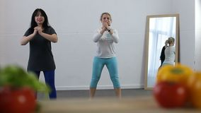 Two sporty women doing fitness exercise at home. Two attractive middle-aged women doing fitness exercises in domestic interior with blurry healthy food on stock footage