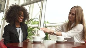 Two attractive mixed race businesswomen talking and making a deal while drinking coffee in the Coffee Shop stock video footage
