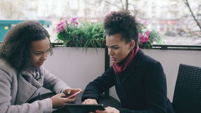 Two attractive mixed race female friends sharing together using smartphone in street cafe outdoors stock footage