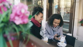 Two attractive mixed race female friends sharing together using smartphone in street cafe outdoors stock video footage
