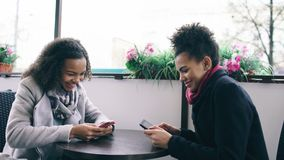 Two attractive mixed race female friends sharing together using smartphone in street cafe outdoors. Two attractive mixed race female friends sharing together Royalty Free Stock Photography